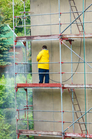 dirtiness: Man cleaning wall. Scaffolding, construction site in progress. Building renovation. Cleaning dirtiness.