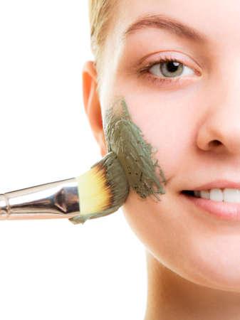 스킨 케어. 얼굴에 브러시 점토 진흙 마스크를 적용하는 여자 절연입니다. 건조한 피부를 돌보는 여자. 미용 치료. 스톡 콘텐츠