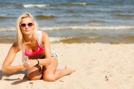 kneeling woman: Pretty young blonde pretty girl on beach kneeling. Woman wearing sunglasses have active time in summer. Summertime and lifestyle concept.