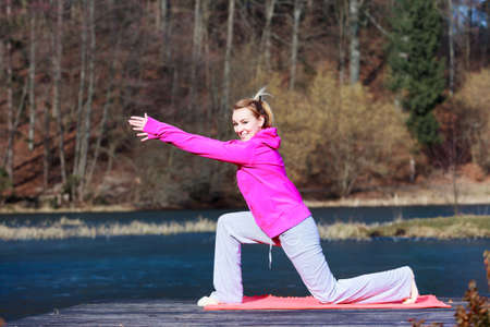 Full length of young woman teenage girl in pink tracksuit doing morning exercise on mat on pier outdoor. Healthy active lifestyle.