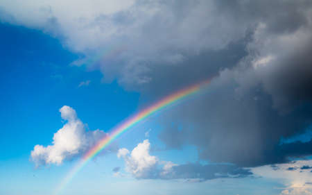 skyscape: Skyscape view on blue cloudy sky with colorful rainbow. Weather.