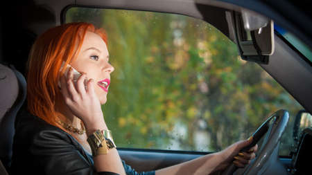 Concept of danger driving. Young woman driver redhaired girl talking on mobile phone smartphone while driving the car. Imagens