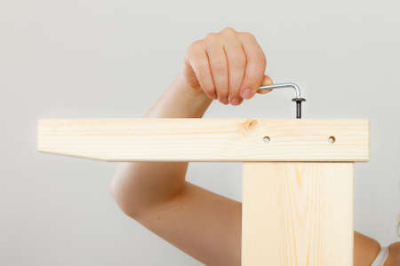 hex key: Human hand assembling wooden furniture using hex key. DIY enthusiast. Home improvement.