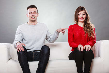 shy woman: Shy woman and man sitting on sofa couch next each other. First date. Attractive girl and handsome guy meeting dating and trying to talk. Male touching picking up female.
