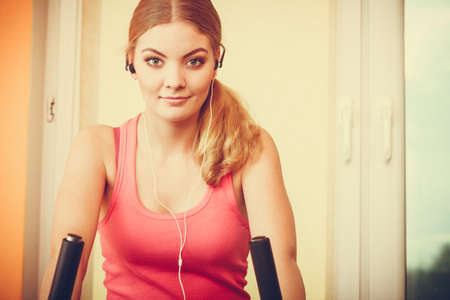 stationary bicycle: Active young woman working out on exercise bike stationary bicycle. Sporty girl training at home listening music. Fitness and weight loss concept.