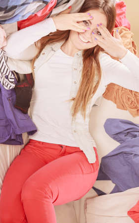 mess: Portrait of happy glad young woman girl lying on stack of clothes covering eyes. Disorder and mess.