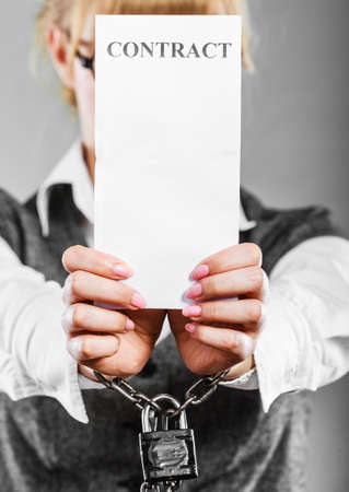 slave labor: Business concept. Serious woman businesswoman with chained hands holding contract, side view grungy background