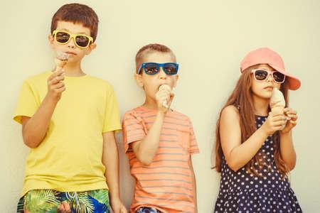 niños comiendo: Niños comiendo helado y suave servir helado. Los niños y niña en gafas de sol disfrutando de las vacaciones de verano vacaciones.