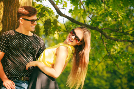 fashionable couple: Love and happiness. Young happy couple lovers wearing sunglasses dating in summer park outdoor. Stock Photo