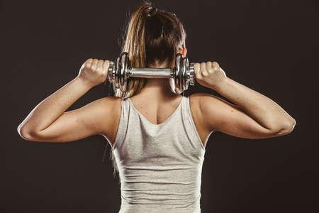 muscle: Fuertes mujer levantando pesas pesos. Chica del ajuste que ejercita ganando músculos de construcción. Fitness y culturismo.
