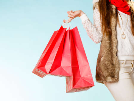 fur: Woman holding shopping bags making gift in christmas time.