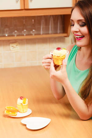gula: Woman drinking coffee and eating delicious gourmet sweet cream cake. Glutton girl sitting in kitchen with hot beverage and cupcake. Appetite and gluttony concept.