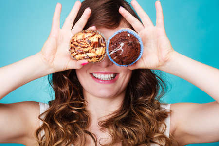 hands covering eyes: Bakery, sweet food and happiness concept. Closeup smiling woman having fun holding cakes in hands covering eyes with cupcakes blue background Stock Photo