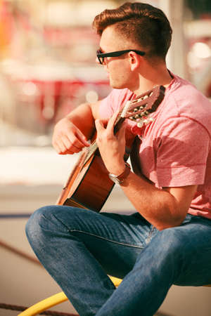 show time: Performance and show time. Young fashionable man wearing sunglasses playing classic guitar outdoor.