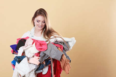 tidying: Woman with stack pile of dirty laundry clothes. Girl cleaning tidying.