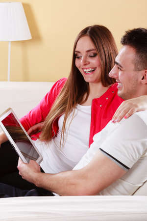 websurfing: modern technologies leisure and relationships concept. Young couple with pc computer tablet sitting on couch at home websurfing on internet