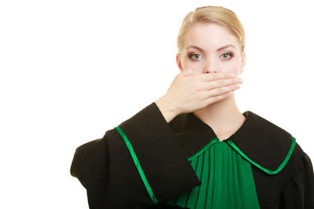 barrister: Confidential information. Law court or justice concept. Woman lawyer barrister wearing classic polish black green gown covering mouth with hand.