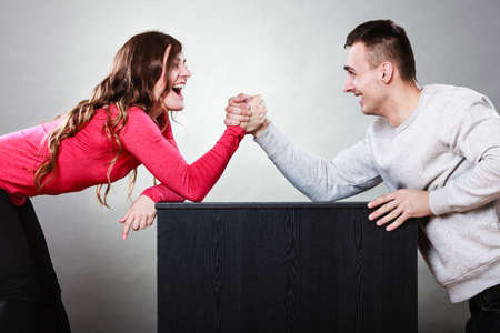 wrestling: Partnership relationship concept. Girlfriend confronts his boyfriend. Woman and man arm wrestling challenge between young couple