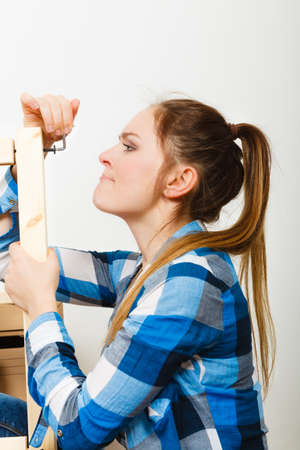 self assembly: Woman assembling wooden furniture using hey key. DIY enthusiast. Young girl doing home improvement.