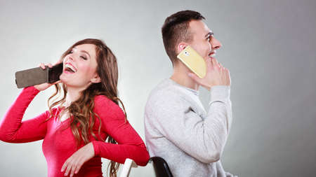phone calls: Young couple talking on mobile phones sitting back to back. Happy smiling woman and joyful man making a call. Wife and husband bored with relationship. Communication concept. Studio shot.