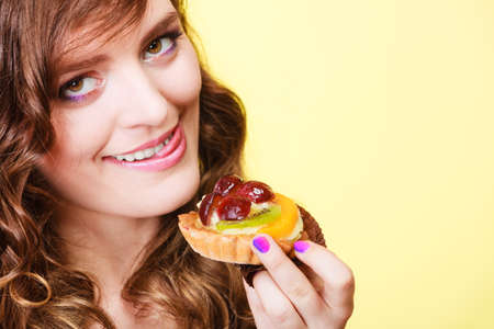 sweetness: Sweetness and happiness concept. Closeup cute funny woman eating fruit cake cupcake having fun sticking tongue yellow background Stock Photo