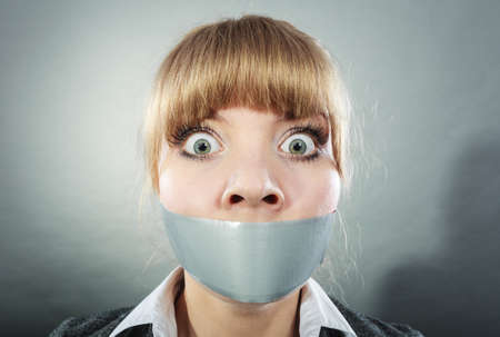 duct: Scared woman with mouth taped shut. Afraid young girl with duct tape on lips. Censorship and freedom of speech concept.