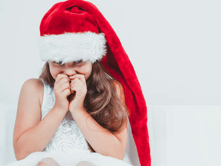 giggling: Cute little girl kid in red santa claus hat and white dress giggling. Chrtistmas holiday season.
