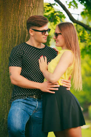 emotional couple: Love and happiness. Young happy couple lovers wearing sunglasses dating in summer park outdoor. Stock Photo