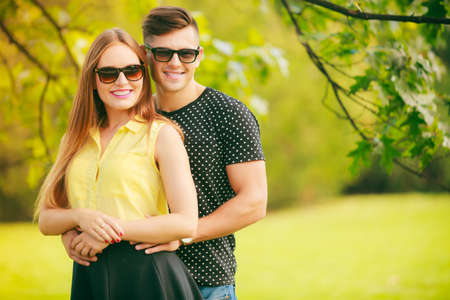 lovers park: Love and happiness. Young happy couple lovers wearing sunglasses dating in summer park outdoor. Stock Photo