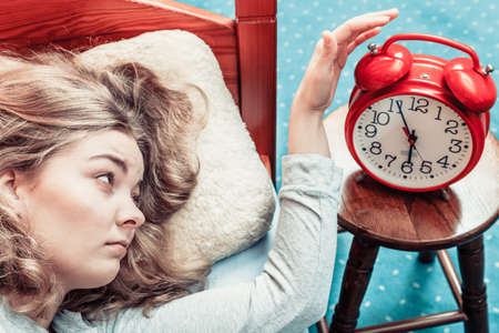 oversleep: Woman waking up in bed turning off alarm clock. Young girl in the morning.
