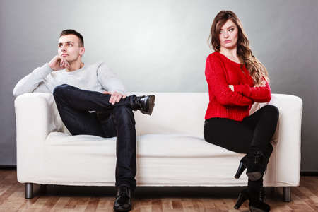relationship problems: Bad relationship concept. Man and woman in disagreement. Young couple after quarrel sitting on sofa