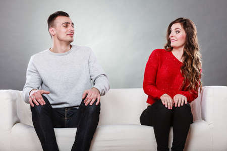 Shy woman and man sitting on sofa couch near each other. First date. Attractive girl and handsome guy meeting dating and trying to talk. Stock Photo