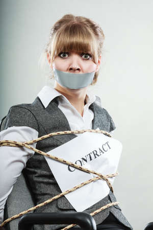 in bondage: Afraid businesswoman bound by contract terms and conditions with mouth taped shut. Scared woman tied to chair become slave. Business and law concept. Stock Photo