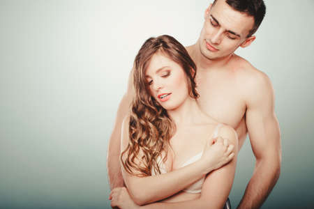 semi nude: Sexy passionate young couple lovers embracing in studio. Handsome muscled half naked semi nude man and pretty gorgeous woman in lingerie. Love and passion.