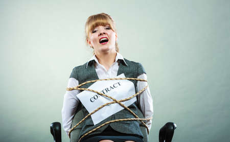 girl tied: Afraid businesswoman bound by contract terms and conditions. Screaming scared woman tied to chair becoming slave. Business and law concept. Stock Photo