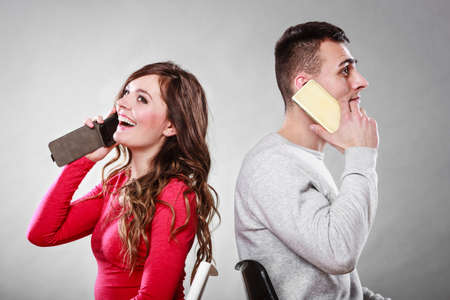 calling: Young couple talking on mobile phones sitting back to back. Happy smiling woman and man making a call. Wife and husband bored with relationship. Communication concept. Studio shot. Stock Photo