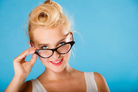 oculist: Optometrista, oculista y el concepto oftalmólogo. Joven rubia retro pin up mujer sonriente con gafas en el fondo azul en el estudio.