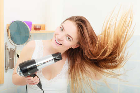air: Haircare. Beautiful long haired woman drying hair in bathroom Stock Photo