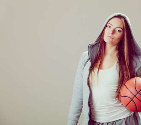 sudadera: Sporty teenager girl wearing hooded sweatshirt holding basketball. Teen sport.