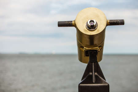 turistic: watching sea ocean trought binoculars telescope on a turistic tower. travel and tourism