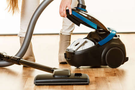 Young woman opening vacuum cleaner on white. Houseworking in home. Standard-Bild