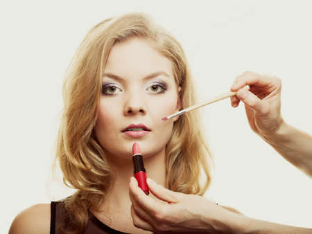 Cosmetic beauty procedures and makeover concept. Makeup artist applying lipstick with accessories tools to woman lips.
