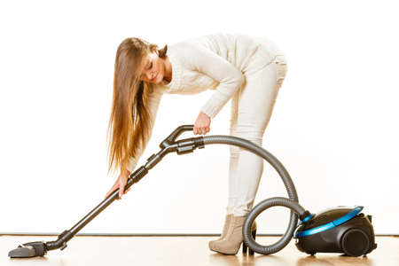 house cleaner: Young woman with vacuum cleaner on white. Houseworking in home. Stock Photo