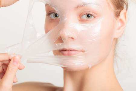 mascarilla: Belleza cosm�ticos cuidado de la piel y el concepto de salud. Primer rostro de mujer joven, muchacha que quita facial mascarilla exfoliante en gris. Descamaci�n Foto de archivo