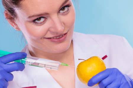 modification: Scientist doctor injecting apple with syringe. Woman chemist holding genetically modified fruit. GM food modification.