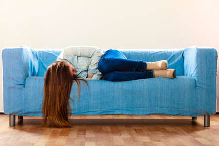 girl lying bed: Loneliness negative emotion concept. Young sad stressed woman lying on couch at home