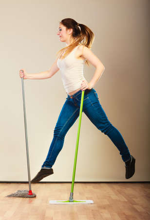 mops: Cleanup housework concept. Funny cleaning lady young woman mopping floor, holding two mops new and old jumping