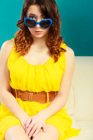yeloow: Summer fashion eyes protection concept. Closeup girl long curly hair yeloow dress in blue heart shaped sunglasses Stock Photo