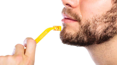 male face profile: Health beauty and skin care concept. Closeup male face profile. Young man guy styling beard holding disposable yellow razor blade white background.