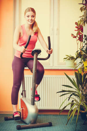 stationary bicycle: Active young woman working out on exercise bike stationary bicycle. Sporty girl training at home. Fitness and weight loss concept. Instagram filtered. Stock Photo